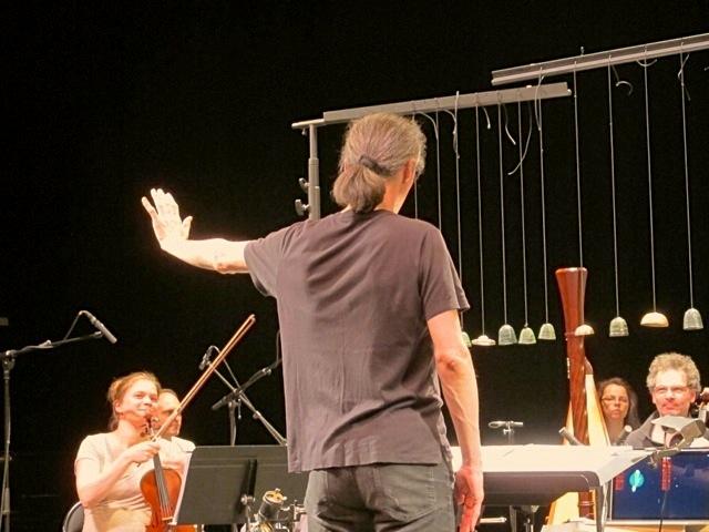 Marc Desmons utilise le dispositif technologique pour jouer avec les sons de l'ensemble. Devant lui, les cloches, utilisées tantôt pour leurs sons percussifs, tantôt comme éléments déclenchant des échantillons pré-enregistrés en entrant dans la zone de captation.